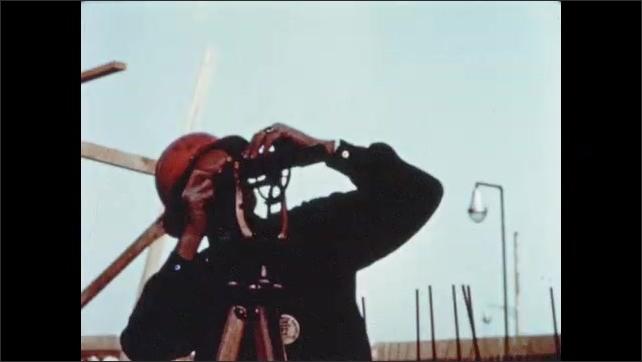 1950s: Hands use ruler to measure steel beam. Man looks through surveyor scope. Man holds wooden stick near steel column. Surveyor checks angle of steel skyscraper frame.