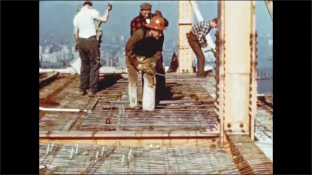1950s: Men unroll wire fabric onto construction site. Men lay steel reinforcing rods on metal fabric.