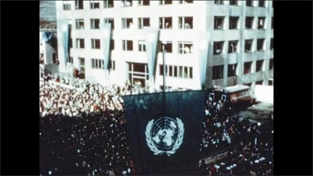 1950s: Men wave hard hats and salute. Flag of United Nations waves in breeze. President Truman of the United States addresses crowd outside of UN building.