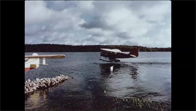 1950s: Two men tie canoe onto bush floatplane at dock. Man closes and locks storage compartment of floatplane. Floatplane moves on the water near dock with parked floatplane. Floatplane takes off.