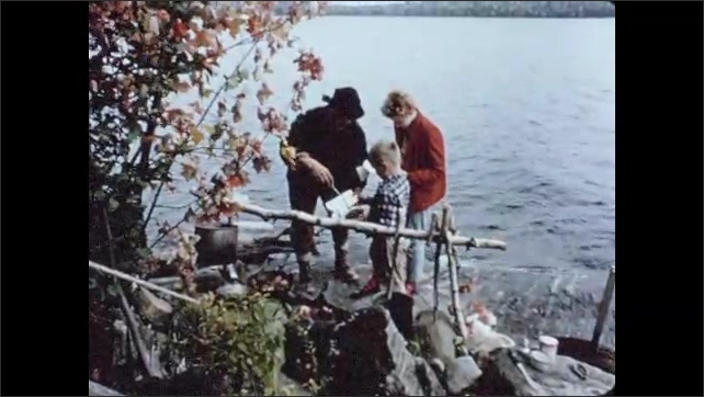 1950s: Hand removes fried fish from pan in improvised camping fire and puts it in another pan. Man serves food to boy and girl by the lake shore. Man puts food on girl's plate and she walks away.