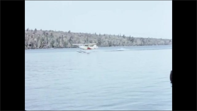 1950s: Family fishes inside canoe, they looks at bush floatplane that moves on the lake, the floatplane stops next to the canoe and a warden comes out.
