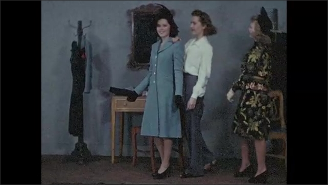 1940s: Dressing room.  Young women stand and walk with hands on each other's shoulders.