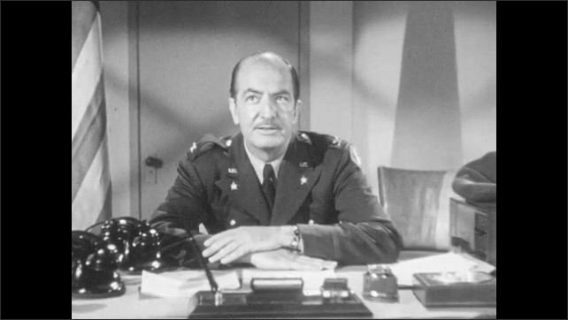 1950s: Two men stand in office. Seated man in military uniform talks.