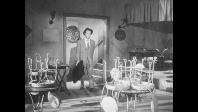 1950s: Man looks at sign for Das Kleine Cafe, enters. Man descends staircase into cafe, chairs upside down on tables and place appears closed. Man approaches bar, slaps bar top, yells for bartender.