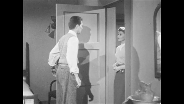 1950s: Woman closes door, walks down hallway, knocks on other door. Man stands up from chair and answers door. Man welcomes woman into room. Man and woman talk.