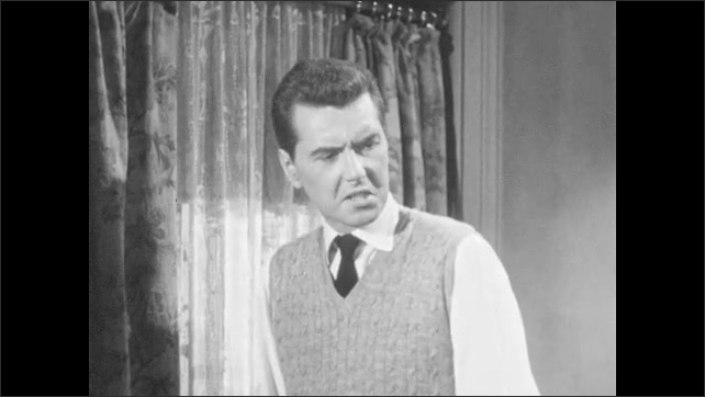 1950s: Man in sweater vest talks and paces room. Woman turns and looks. Man talks.