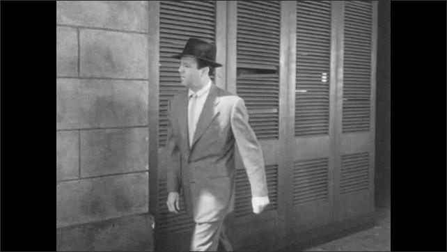 1950s: Man peaks into building through broken shutters, sees abandoned/empty barroom. Man walks away from broken shutters and walks towards, and enters, Das Kleine Cafe.
