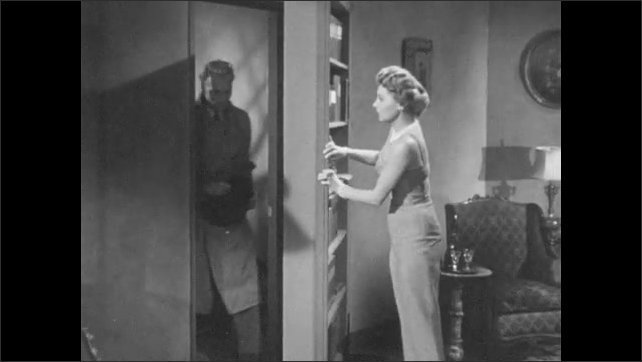 1950s: Woman enters room and locks door behind her. Woman knocks on bookcase, then opens it revealing secret passage. Man enters from secret passage. Man talks to woman, woman prepare cigarette.