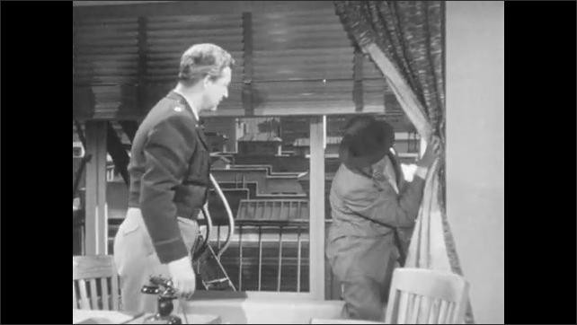 1950s: Man in office, man walks down fire escape in background, knocks on window, man enters window, men sit and talk.
