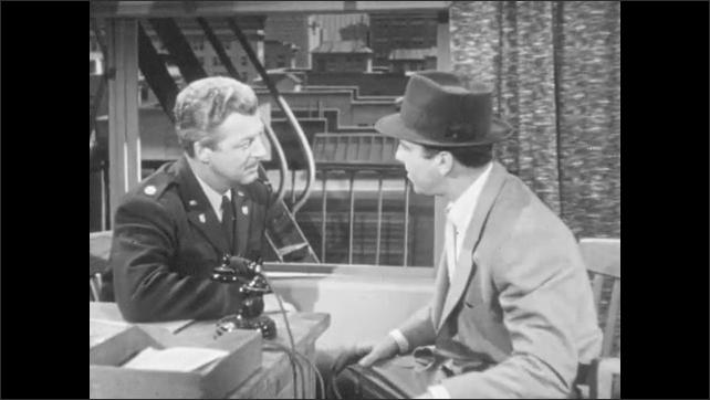 1950s: Men talking at desk.