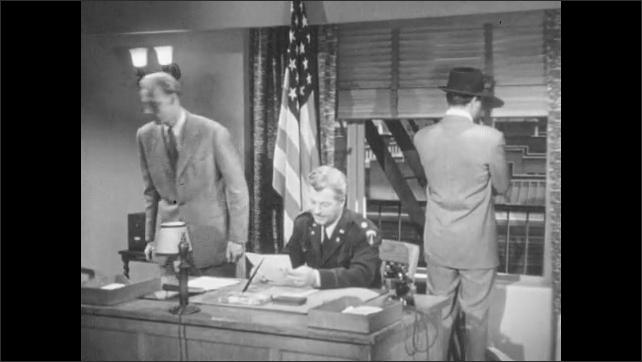 1950s: Man enters door. Men at desk, man stands and turns around. Man approaches desk, hands paper to man. Man walks out of door. Man stands, talks to other man. Man listens through door.