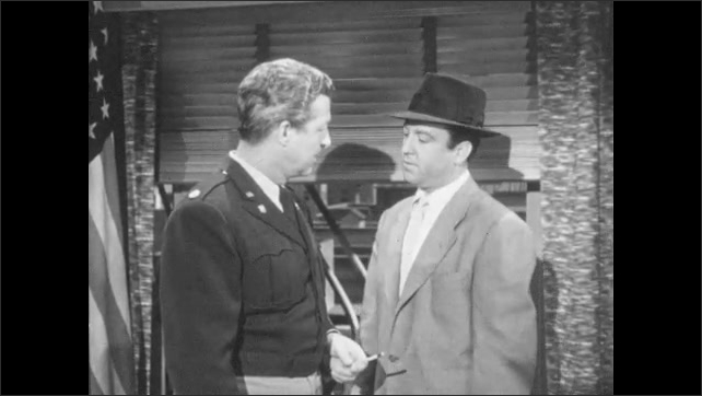 1950s: Men talk in office. Man listening through door, man walks away.
