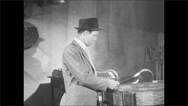 1950s: Man looks at instruments, starts to play zither with sticks. Man playing, people enter doorway in background. Man looks up. Woman speaks in doorway.