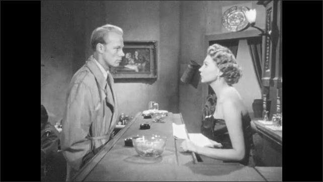 1950s: Pan, man walks through restaurant, talks to woman at bar, man and woman exit through door.