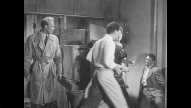 1950s: Man walks through door. Close up, man tied to pipe. People walk through door. Man talks. People approach man, man holds gun on woman, unties man from pipe.