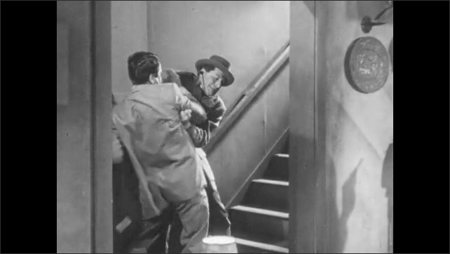 1950s: Men stand up from instruments, man points gun at them. Man gets up from table, runs to stairs, man attacks man in staircase, pushes man into room, reads note.