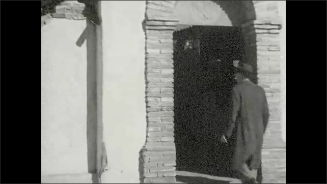 "1930s: Building reads ""MISSION SAN JUAN CAPISTRANO.""  Man walks through mission.  Garden.  Man feeds birds."
