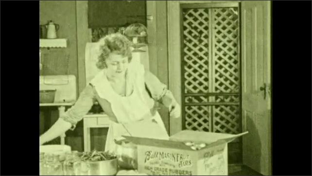 1930s: Woman in kitchen, opens box. Close up of woman. Hand takes paper from box. Woman reads paper, takes out jar. Woman looks at jar. Takes out jars.