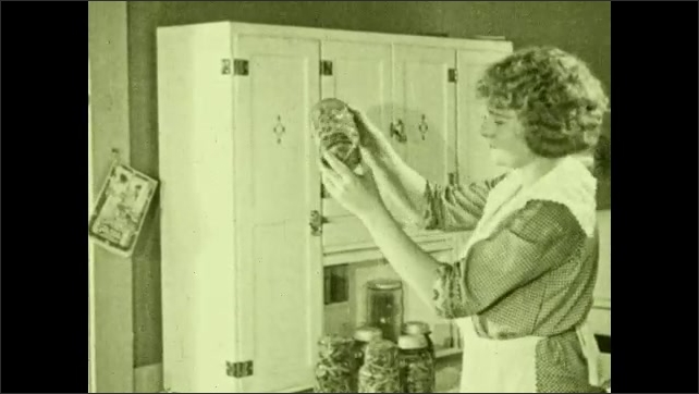 1930s: Woman picks up jars, inspects contents. Hands rotate jar.