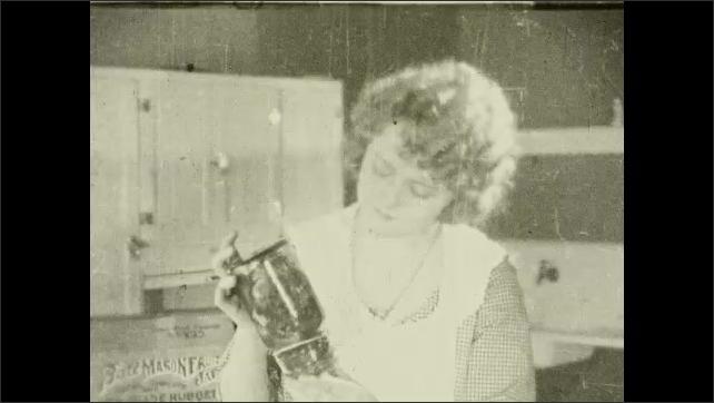 1930s: Woman puts jars in pot. Intertitle. Woman inspects jars. Intertitle. Woman inspects jars.