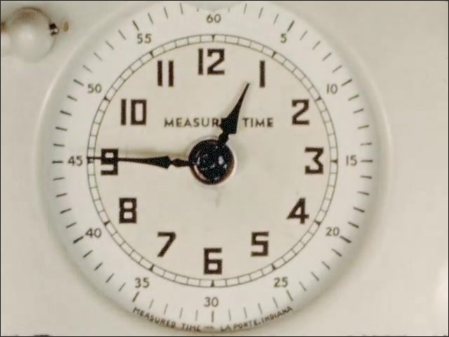 1940s: UNITED STATES: hand moves along paper in book. Speeded up clock on wall. Hand lifts lid off pan. Hot jars inside pan