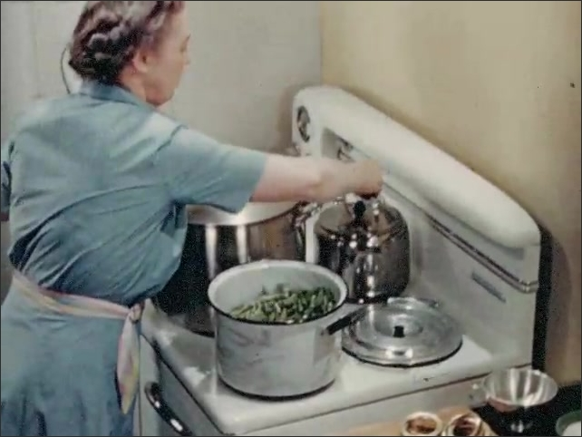 1940s: UNITED STATES: ladies sit at table to work. Lady pre heats string beans on stove. Lady adds hot water to pan. Clock on wall. Clock hands move fast
