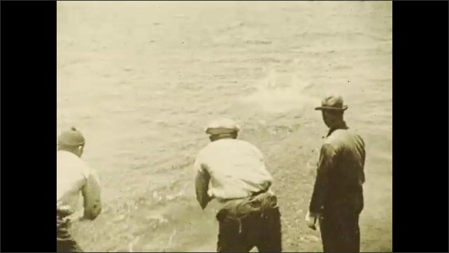 1930s: Fish on deck of boat. Men reel in fishing lines. Man pulls fish into boat.