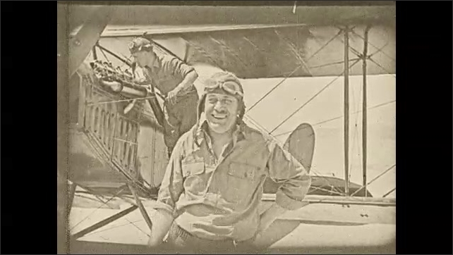 1930s: Two men disembark a biplane in the desert. One waves and smiles. Two goatherds fall to their knees, bowing.