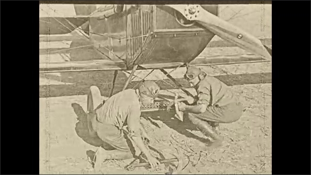 1930s: Two men remove chains and anchors from the wheels of an airplane.