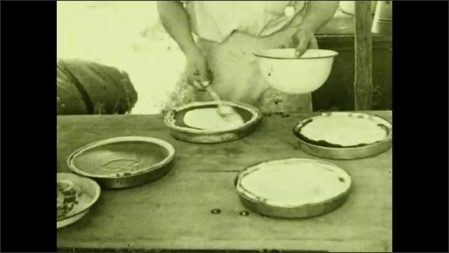 1930s: UNITED STATES: man bakes in tent. Cowboy in tent. Man puts cream on pie. Come and Get it.