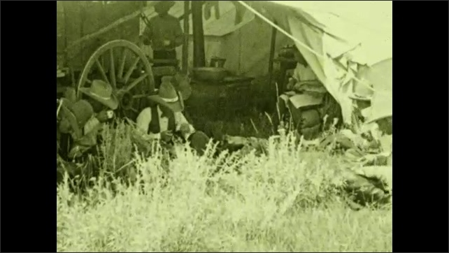 1930s: UNITED STATES: ranchers rest by cart wheel. Cowboys eat by tent. Man eats rice. Men sit on ground and eat