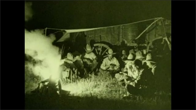 1930s: UNITED STATES: cowboys sit around camp fire at night.