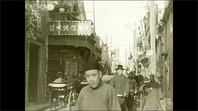 1930s: People walk around city. Man drives horse drawn cart. People walk under archway. People ride bicycles and rickshaws through city. Intertitle card. Women and children walk down street.