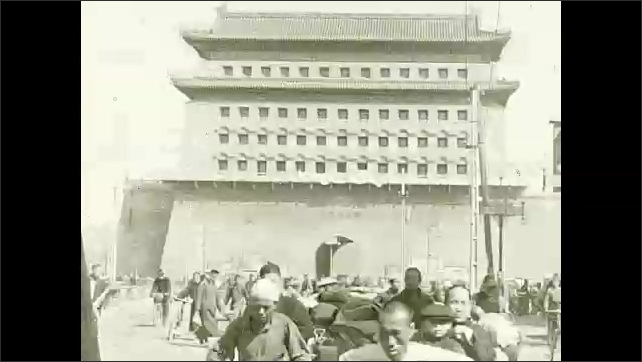 1930s: Woman with bounds feet walks through town. People travel around city streets. Intertitle card. People walk outside gateway, man runs down street.