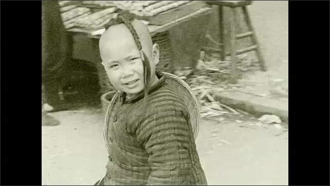 1930s: Man pierces man's ear. Children walk around outside. Tall building. Mounds of dirt.