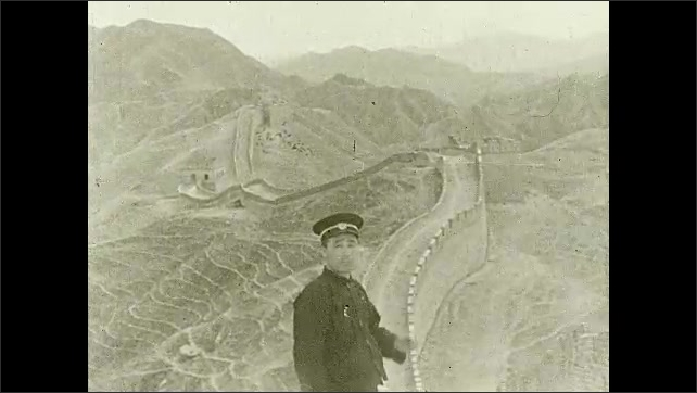 1930s: Man smokes cigarette on top of Great Wall of China. People walk along wall.