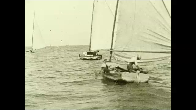 1930s: Small, single-person operated sailboats in sea. Man in each sailboat tosses nets over side of boat.