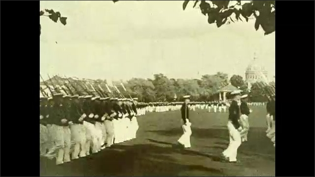 1930s: Men in uniform with rifles slung over shoulders, march in formation across field. Soldier salutes. Color guard carry flags. Soldiers march across promenade.