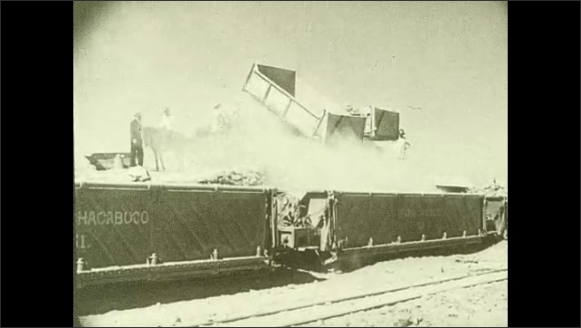 1930s: CHILE: powder in hands. Quarry trucks load up train. The ore is crushed