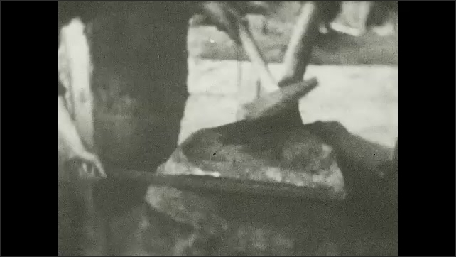 1930s: Men hammer and shape large drill bit on anvil. Illustrated placard with words.