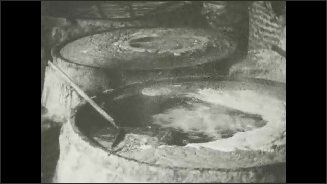 1930s: Illustrated placard with words. Flames lick iron basin. Brine boils in iron basin. Illustrated placard with words. Man skims scum and froth from surface of boiling brine.