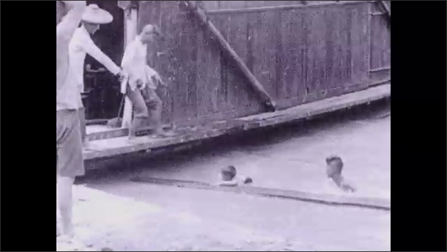 1930s: Boy climbs onto plank and adults pull him out of water.