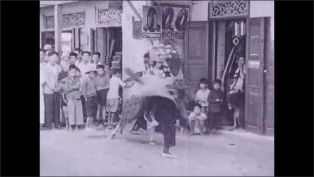 1930s: Chinese children love to masquerade. Child in costume. Children in dragon costume. Children applaud.