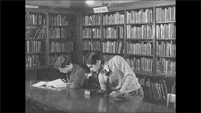 1930s: UNITED STATES: vocation section in library. Boy takes book from library shelf. Boy sits at table with book. Boys flicks through book