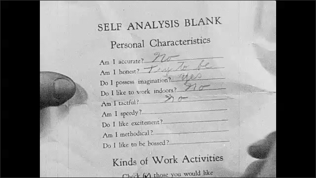 1930s: UNITED STATES: boy completes self analysis form. Hand fills in form. Kinds of work assessment. Boy shakes head.