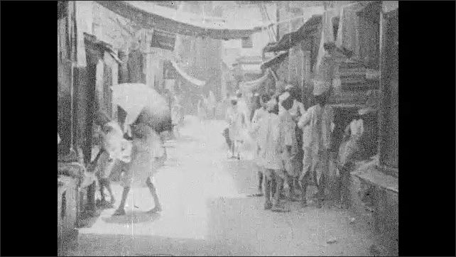 INDIA 1930s: Intertitle card. People walk down street, stand outside vendor stalls.