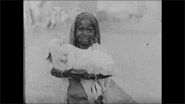INDIA 1930s: Intertitle card. Girl holds lambs, smiles.