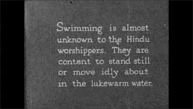 INDIA 1930s: People bath and wash clothing in the Ganges river. Intertitle card.