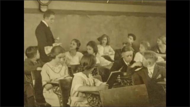 1920s: Words written in cursive on paper. Schoolyard. Teacher walks around classroom talking to students. Hands boy at desk piece of paper. Words written in cursive on paper.
